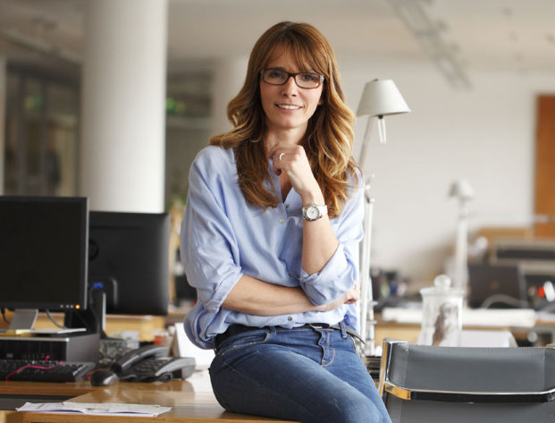 Confident woman sitting on a desk smiling